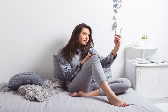 Young woman at home in bed taking a selfie on smart phone