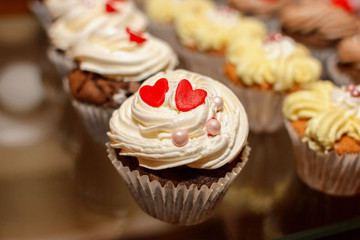 Closeup of cupcake decorated with red hearts and glaze pearls