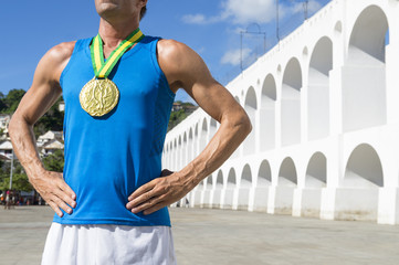 Athlete with gold medal stands at the Arcos da Lapa Arches in Rio de Janeiro Brazil