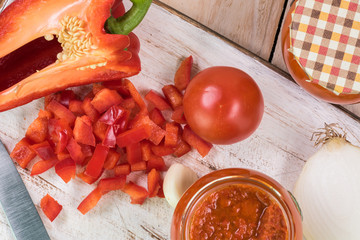 Ingredients for red roasted pepper spread and open glass jar with roasted red pepper spread.