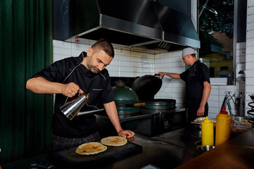 Two chefs in black uniform cook in a restaurant kitchen.