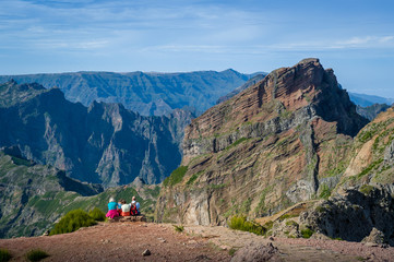 Group of tourists is sitting on the cliff and looking at the mountain landscape.