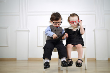 boy in black glasses with tablet computer and girl in red glasses talking on the mobile phone
