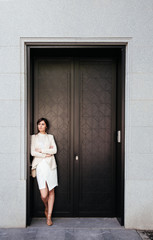 Attractive businesswoman with arms crossed standing at doorway