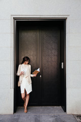 Young businesswoman with coffee to fo looking at notebook