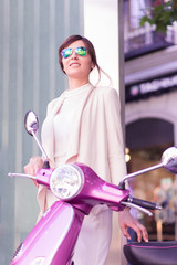 Elegant smiling businesswoman with scooter in the street