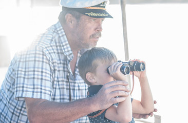 Boat captain with boy tourist looking through binoculars on boat trip, Cape Town, South Africa