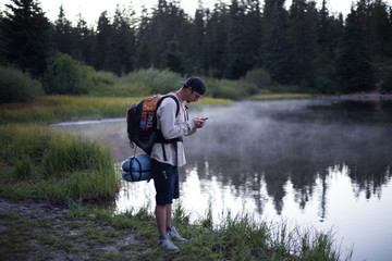 Male hiker reading smartphone text by misty lake, Mount Hood National Forest, Oregon, USA