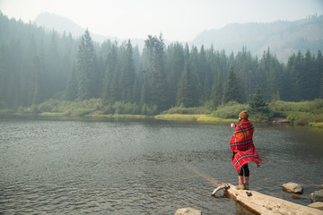Woman wrapped in tartan blanket drinking coffee by misty lake, Mount Hood National Forest, Oregon, USA