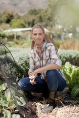 Portrait of mature woman crouching in garden