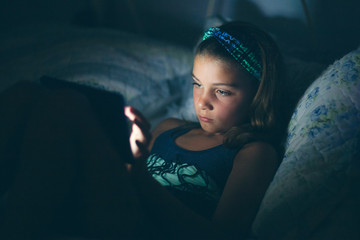 Girl using tablet computer in bed