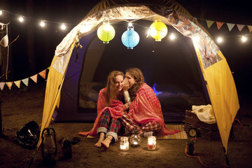Girls whispering in camping tent at night