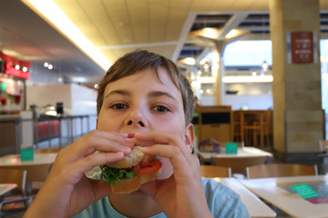 Little boy is eating sandwich at fast food cafe.