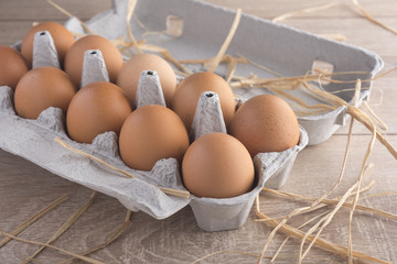 Chicken eggs in the package on a wooden table.