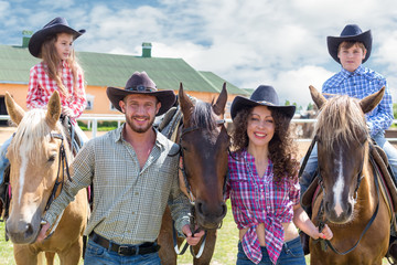 cowboy family of four with horses closeup
