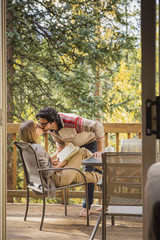 Hispanic couple kissing on patio beyond doorway