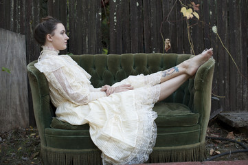 Caucasian woman wearing vintage gown on backyard sofa