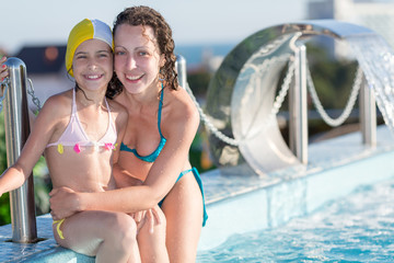 mother and daughter sitting on the edge of the rooftop swimming pool