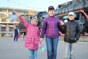 Happy mother with son and daughter near a sports stadium and a monument of the locomotive