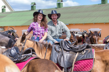cowboy couple smiling among horses