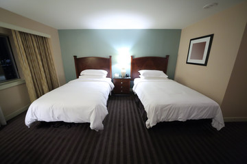 Small stylish bedroom with two beds and lamps in Hilton Boston Back Bay Hotel.