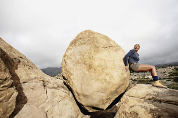 Black woman pushing large rock