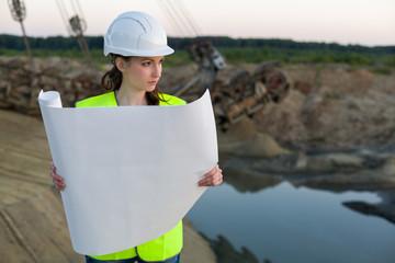 female worker examines cheme on background of career Stacker