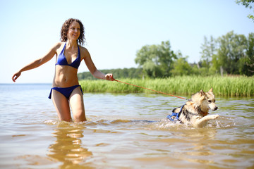 Young woman in a swimsuit runs out of the river with a big dog