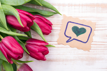 A bouquet of tulips and ornamental card with heart on a wooden background