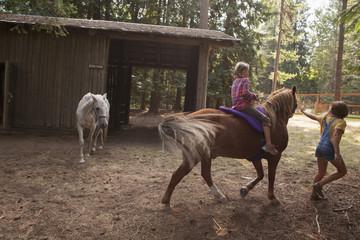 Caucasian children riding horse on farm