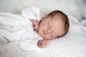Portrait image of a new born baby boy, laying on a white blanket.