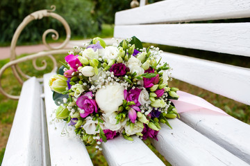 Beautiful bridal bouquet of flowers on wooden bench