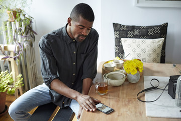 Black man using cell phone at table