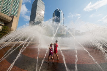 Mother and her daughter are dancing together into the fountain a