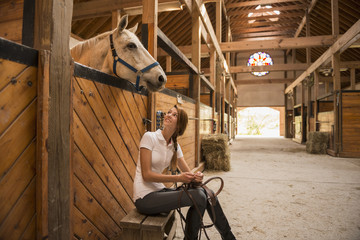 Caucasian girl sitting with horse in stable
