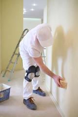 Builder polishing the wall using a sanding sponge