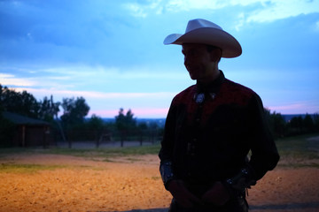 Silhouette of a man in a cowboy hat on a background of a sunset in a horse based Avanpost