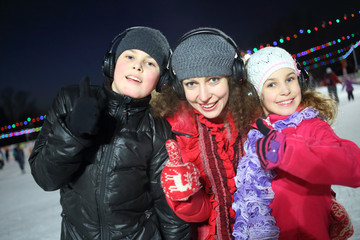 Happy mother with son and daughter make excellent gesture on the silent disco skating