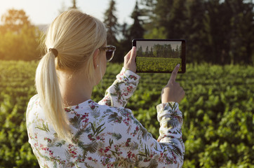 Beautiful blonde taking picture with tablet in nature