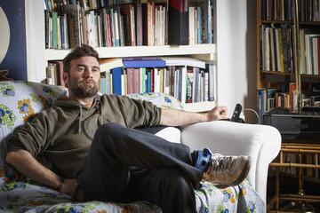 Caucasian man sitting on sofa in living room