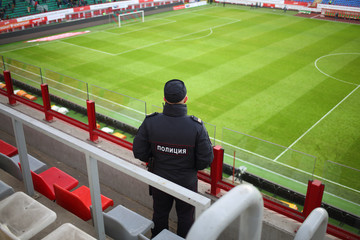 Policeman is standing at grandstand on Locomotive football stadium.