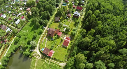 Cottage settlement near pond and forest at summer sunny day. Aerial view