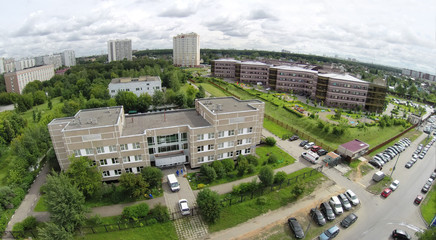 Side elevation of diagnostic clinic against townscape at summer cloudy day in Solntsevo. Aerial view.