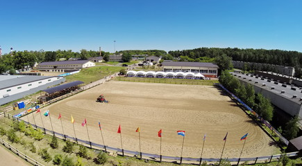 Tractor prepares sand on equestrian arena of sports complex Sozidatel before Russian Championship for Dzhigitovka at sunny summer day. Aerial view. Photo with noise from action camera.
