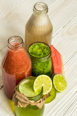 green and red smoothies in a jar with lime, kiwi