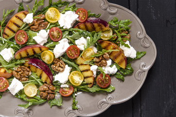 Salad with arugula and cherry tomatoes feta peaches with balsamic cream