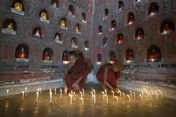 Asian monks-in-training lighting candles in ancient temple
