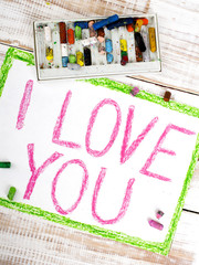 words  I LOVE YOU written in crayon on paper