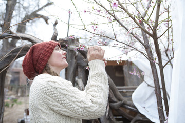 Woman admiring flowering tree branches in garden
