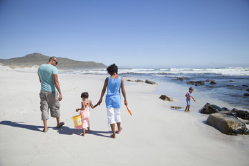 Mixed race family walking on beach